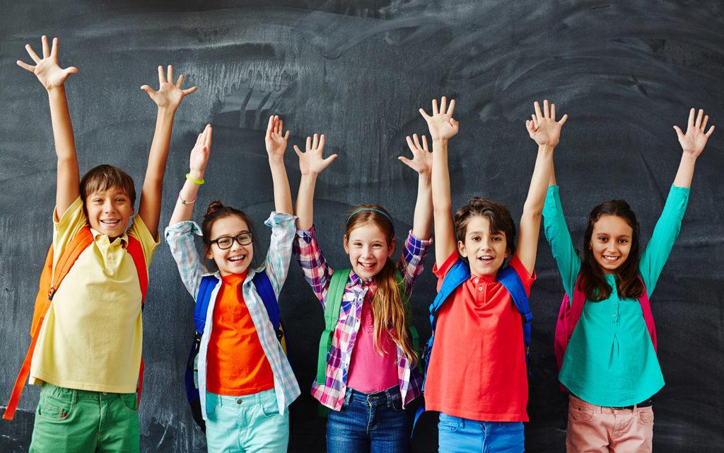 Kinder mit hochgeworfenen Armen vor einer Schultafel