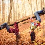 zwei Mädchen turnen auf einem Baum im Wald