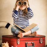 Mädchen mit Fernglas auf Koffer