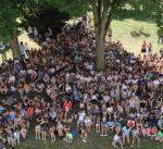 Eine große Anzahl an Schülerinnen und Schülern sitzen in der Wiese vor der Schule.