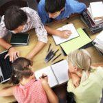 Vier Schüler von oben fotografiert an einem Tisch sitzend arbeiten an einem Laptop.