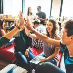 Gruppe von SchülerInnen sitzen im Kreis und geben einander ein High Five