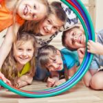 Fünf Kinder halten einige Hulahupp Reifen in Zimmer mit Laminatboden und schauen lachend durch die Reifen