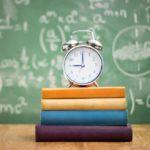 Wecker auf Schulbüchern vor Schultafel