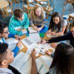 Gruppe von Schülerinnen und Schülern sitzen um einen Rundtisch und lernen gemeinsam.