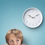 Kind schaut von unten auf große weiße Uhr.