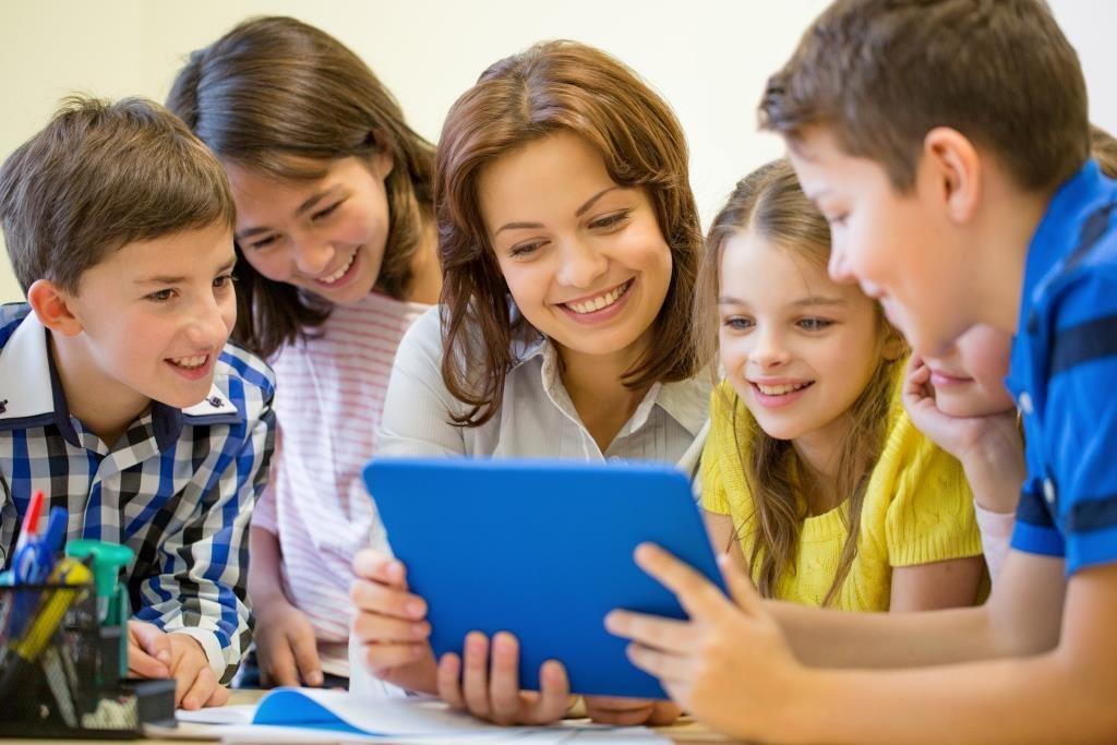 Lachende Lehrerin mit Tablet in der Hand und jungen SchülerInnen rund um sie.