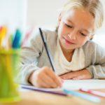 Blondes Mädchen zeichnet mit Buntstiften.