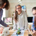 4 Schülerinnen programmieren kleinen Roboter mit Tablets.