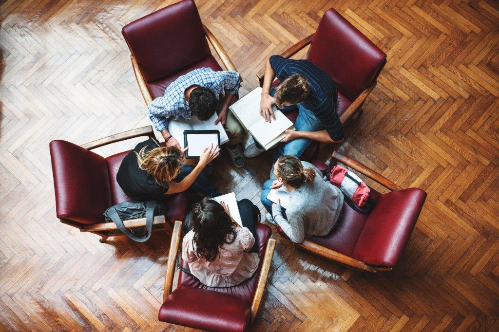 Fünf Schülerinnen und Schüler von oben fotografiert sitzen auf roten Polstersesseln im Kreis mit Unterlagen auf den Oberschenkeln und beraten sich