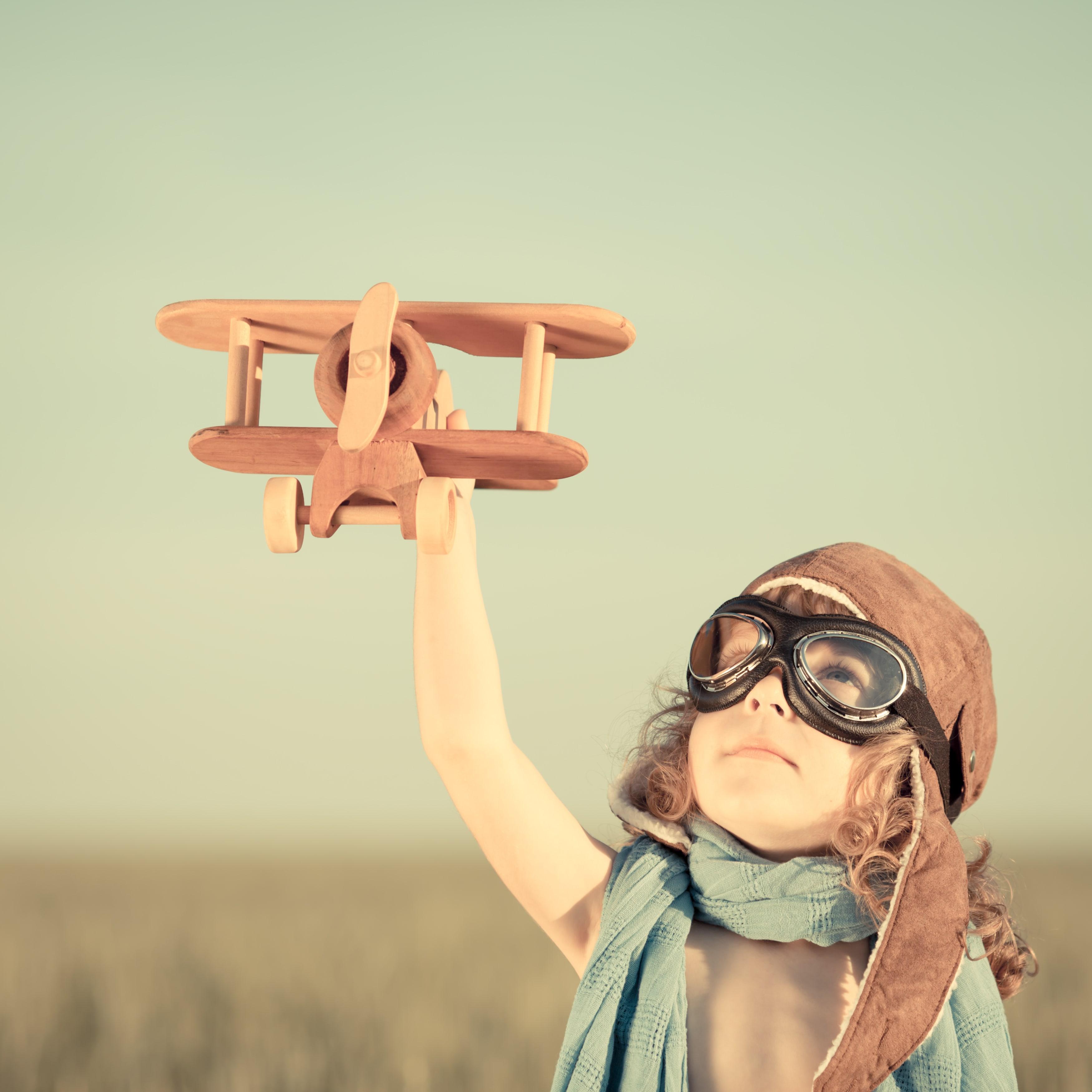 Junges Mädchen mit Pilotenmütze und Pilotenbrille hält ein Holzflugzeug mit gestrecktem Arm in die Luft