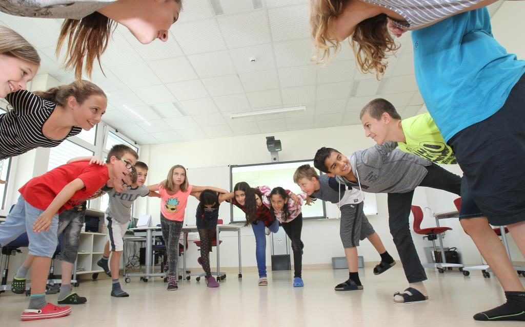 Gruppe von Schülerinnen und Schülern stehen im Klassenzimmer Arm in Arm im Kreis.