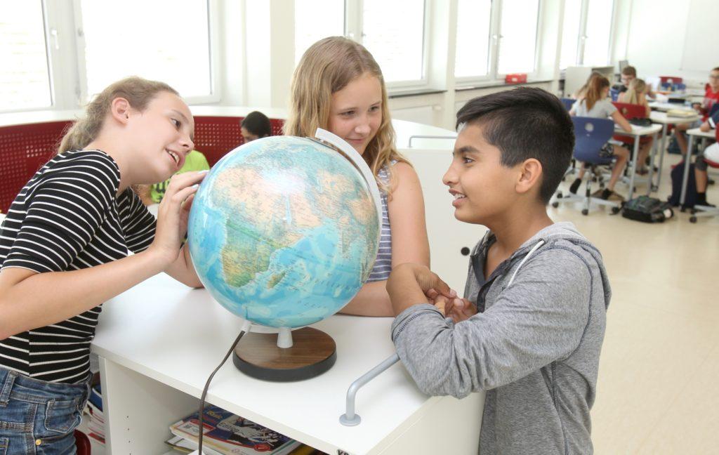Drei Schülerinnen und Schüler stehen um einen Globus und reden miteinander.