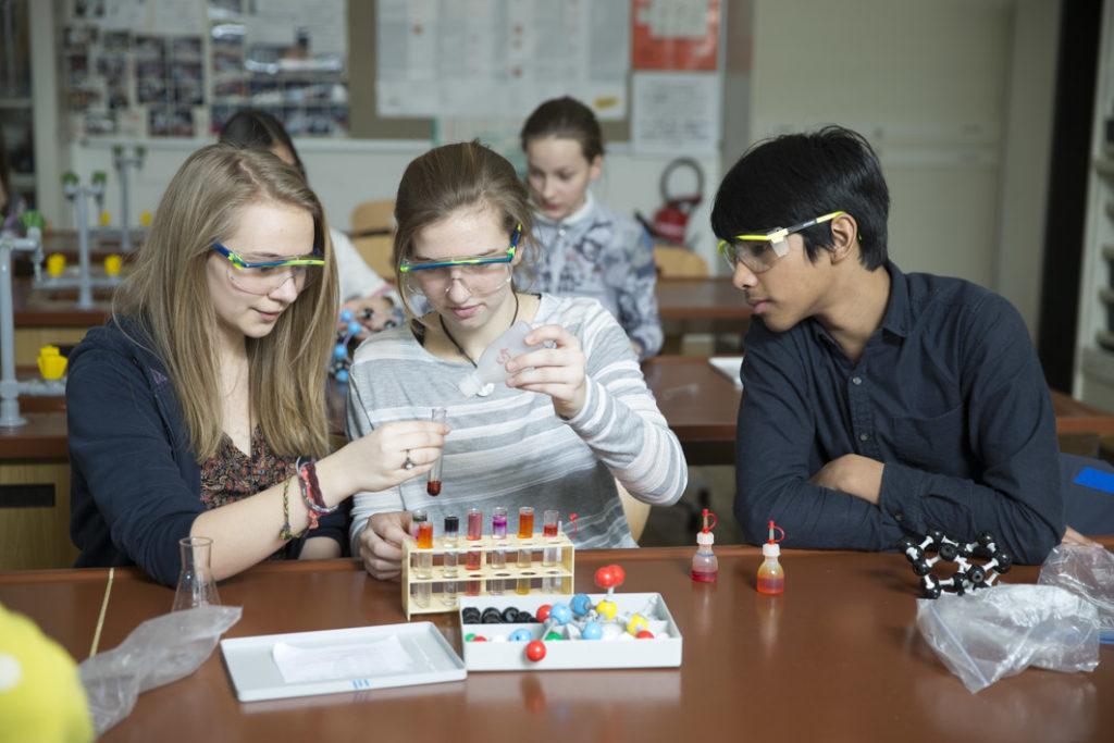 3 SchülerInnen arbeiten im Chemiesaal an einem Experiment mit verschiedenen Flüssigkeiten