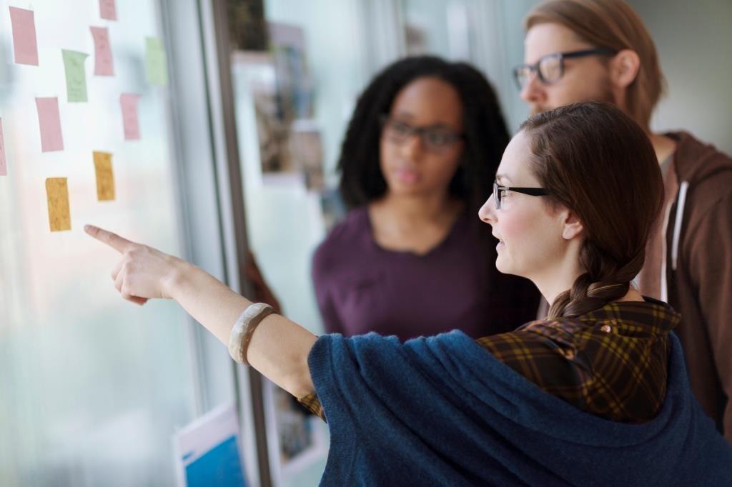 Drei Studtenten stehen vor einer Wand mit Post-its und besprechen Ideen.