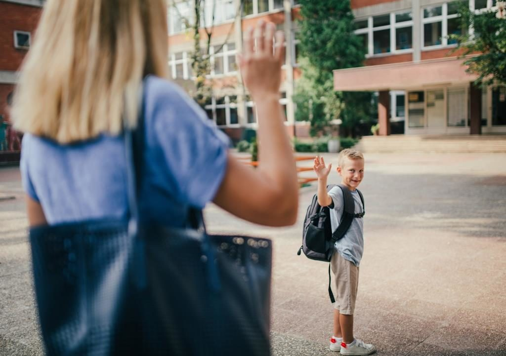 Bub steht mit Rucksack vor dem Schuleingang und winkt seiner Mutter lächelnd zum Abschied.