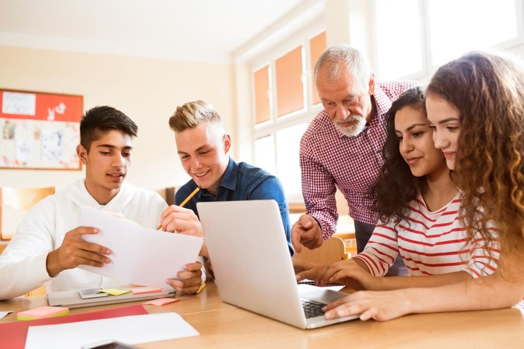Eine Gruppe Schülerinnen und Schüler sitzt um einen Tisch und lernt gemeinsam. Ein älterer Lehrer steht hinter einer Schülerin und erklärt etwas.