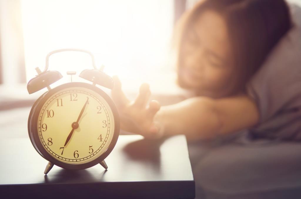 Frau greift nach dem Aufwachen zum Wecker.