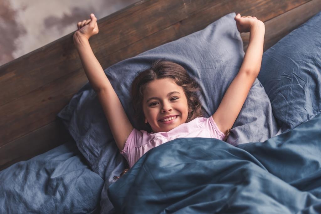 Dunkelhaariges Mädchen liegt nach dem Aufwachen lächelnd im Bett und streckt die Arme fröhlich über den Kopf.