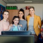 Lächelnde Schülerinnen stehtn um eine freundliche Lehrerin. Alle lächeln in die Kamera.