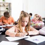 Kinder sitzen im Klassenzimmer an ihren Tischen nebeneinander und schreiben bzw. zeichnen konzentriert.