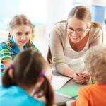 Lehrerin hilft einer Gruppe von Volksschülerinnen.