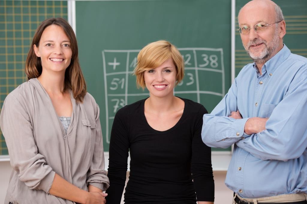 Zwei Lehrerinnen und ein Lehrer stehen freundlich lächelnd vor eine Schultafel.