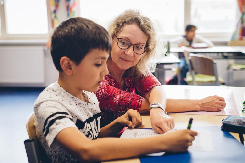 Lehrerin sitzt in Schulklasse neben einem Schüler welcher vor einer Schulaufgabe sitzt und überlegt