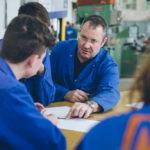 HTL-Lehrer erklärt Schülerinnen und Schülern in der Werkstatt einen Plan.