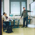 Lehrer vor einer Schultafel zeigt und erklärt seinen Schülern etwas darauf