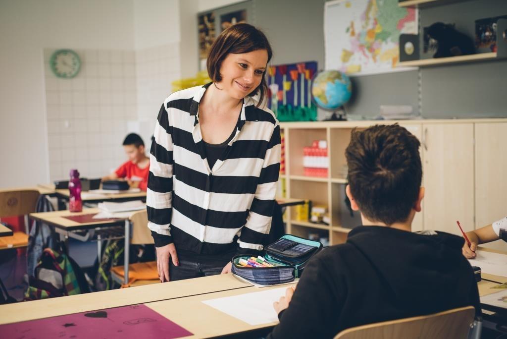 Lehrerin steht lächelnd vor einem Schüler im Klassenzimmer.