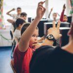 Schulklasse vor Computern gibt Handzeichen auf Frage eines Lehrers