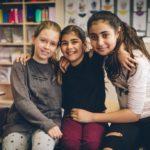 Drei Schülerinnen sitzen Arm in Arm und lachend auf einem Tisch im Klassenzimmer.