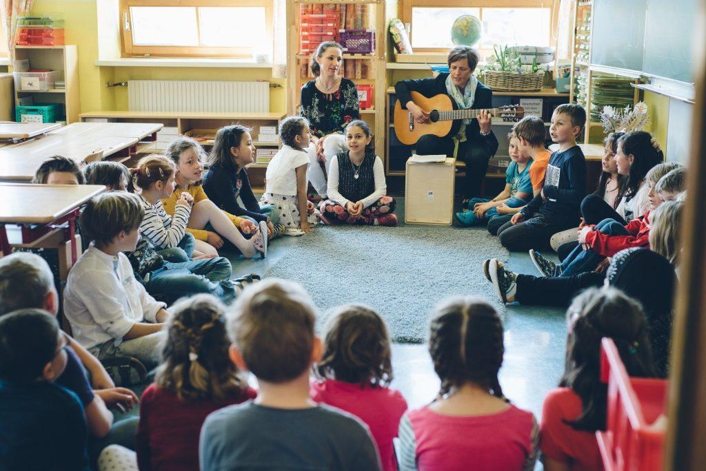 Kleine Kinder Sitzen im Kreis auf dem Boden und singen mit der Lehrerin ein Lied, welche dabei Gitarre spielt