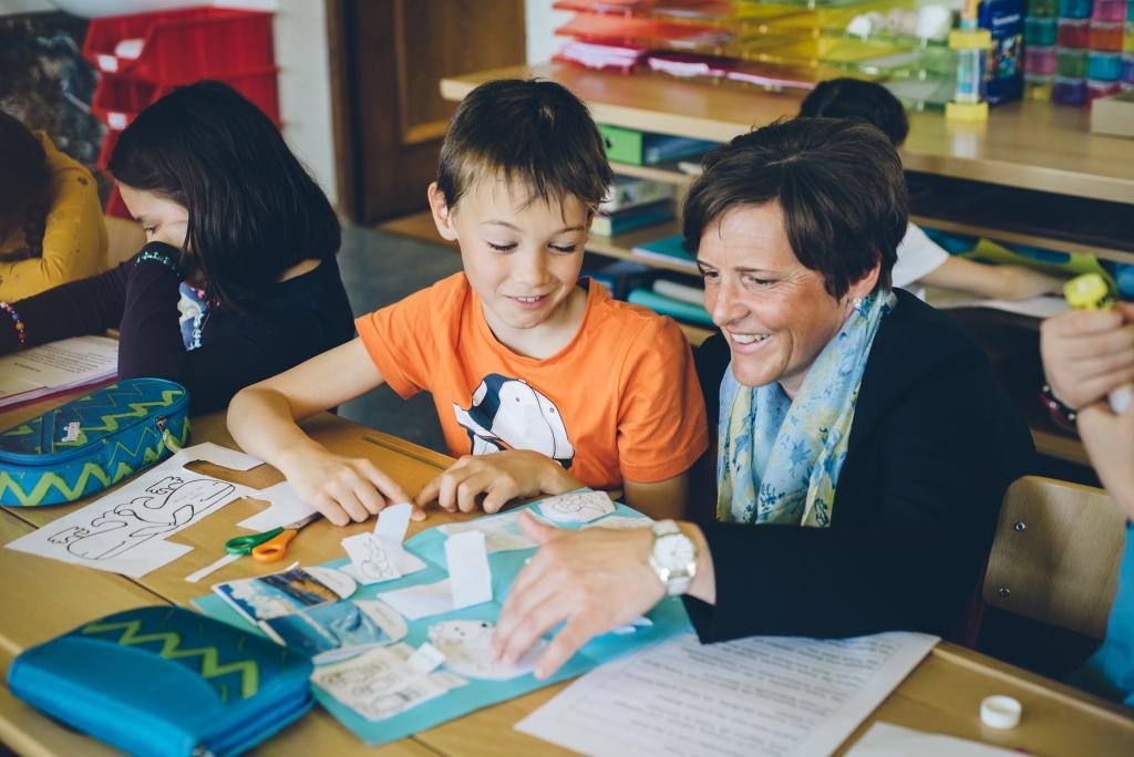 Lehrerin hilft kleinem Bub beim basteln einer Collage