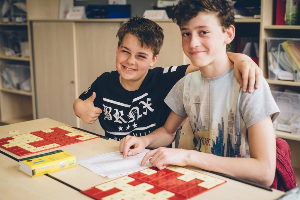 Zwei Schüler versuchen an Ihrem Schultisch ein Zahlenrätsel zu lösen