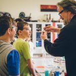 Chemielehrer erklärt Kindern mit Schutzbrillen etwas Anhand eines Kronkorken