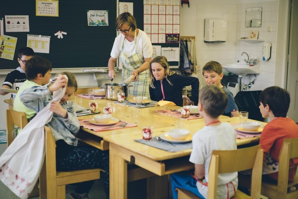 Lehrerin und Schülerinnen beim Essen im Klassenzimmer.