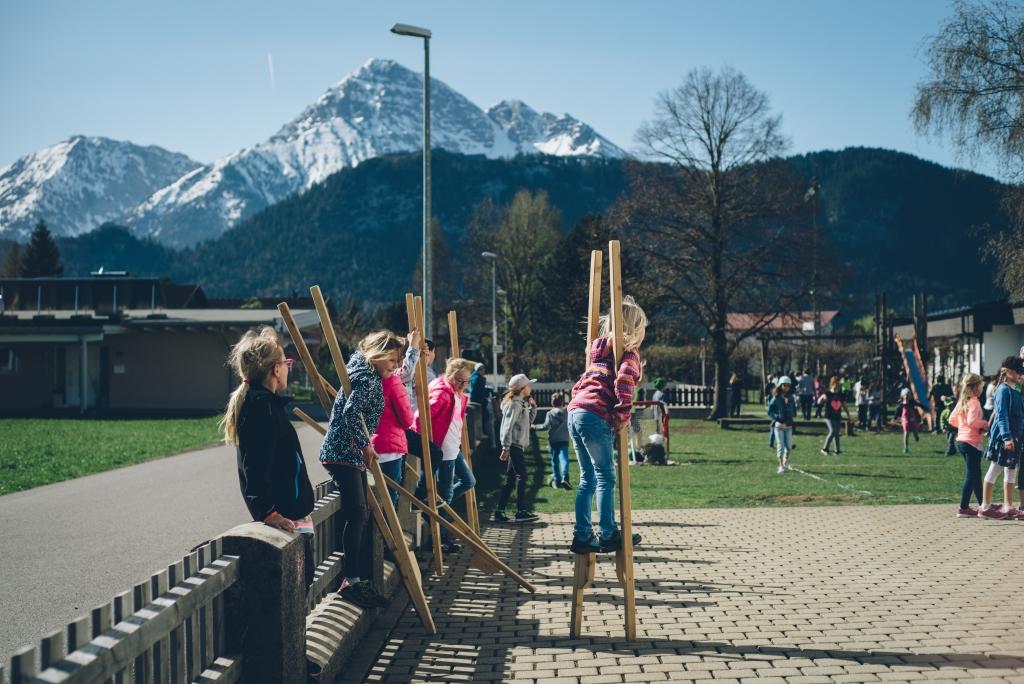 Schulkinder laufen auf Stelzen im Schulhof mit Bergen im Hintergrund