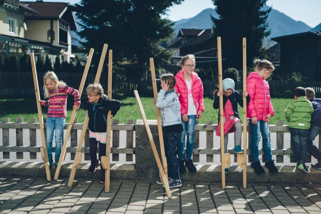 SchülerInnen im Pausenhof versuchen sich beim Stelzengehen