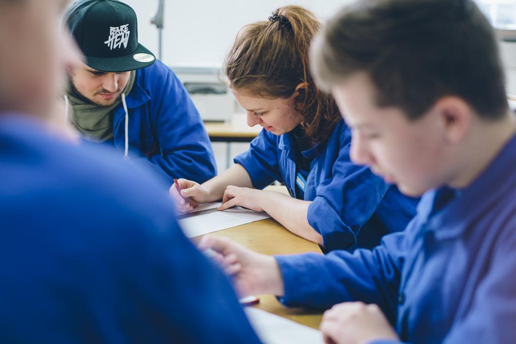 Vier Schüler im Blaumann sitzen vor einer Schulaufgabe am Tisch