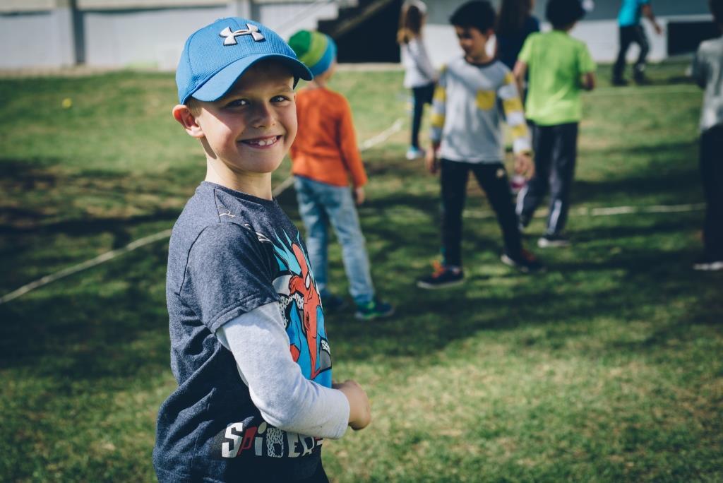 Bub mit Kappe steht im Schulgarten und lächelt in die Kamera. Hinter ihm spielen weitere Kinder im Garten.