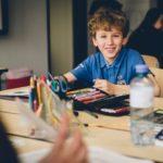 Schulbub mit seiner Stiftemappe am Schultisch