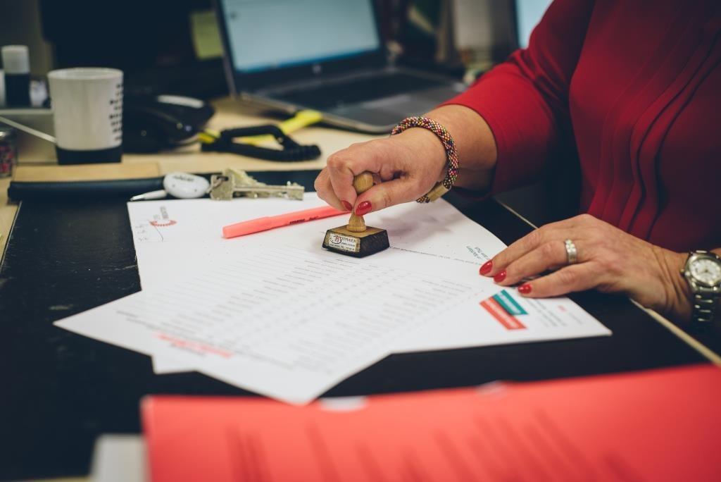 Man sieht die Hand einer Direktorin, die ein Dokument abstempelt.