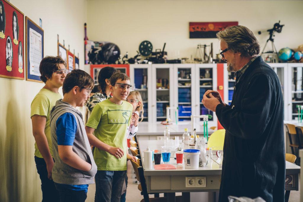Chemieprofessor erklärt Schülern ein durchgeführtes Experiment.
