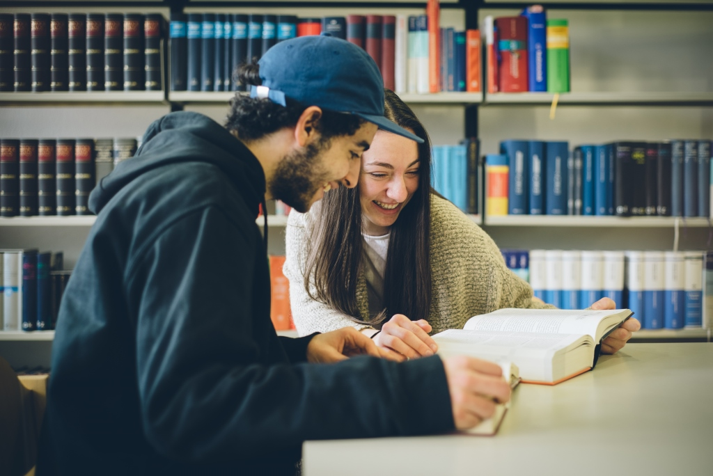 Zwei junge Erwachsene lernen in der Bibliothek
