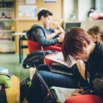 Drei Schülerinnen und Schüler lernen selbstständig mit Lehrbüchern und Laptops nebeneinander auf einer Couch bzw. in einem Lesesessel.