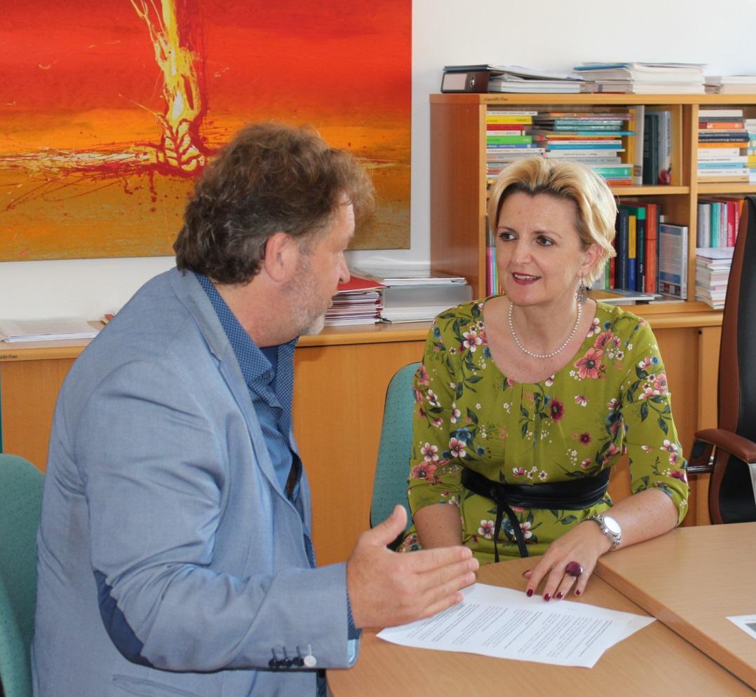 Alfred Lehner und Sandra Steiner sitzen an einem Tisch und sind im Gespräch.