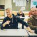 Ältere Schüler sitzen in der Klassen und arbeiten aktiv im Unterricht mit.