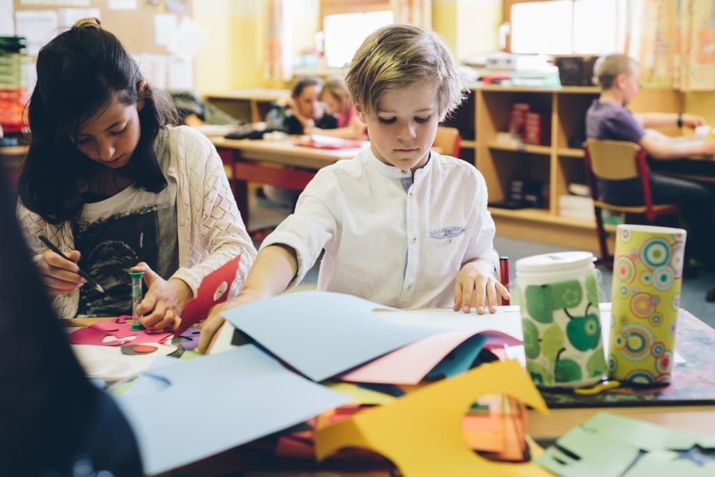 Schülerinnen und Schüler der Volksschule Lechaschau lernen im Klassenzimmer an Tischinseln.
